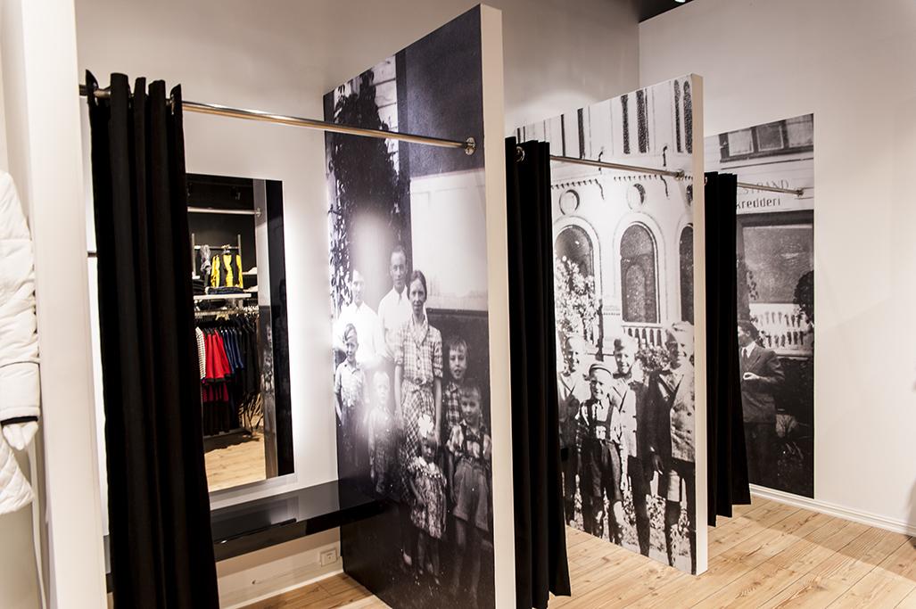 Modebutik med butiksdesign og butiksinventar, og hvor luksus prøverum er indrettet med grafiske elementer, siddehylde og spejle med lys. Butiksinventar. Butiksindretning.