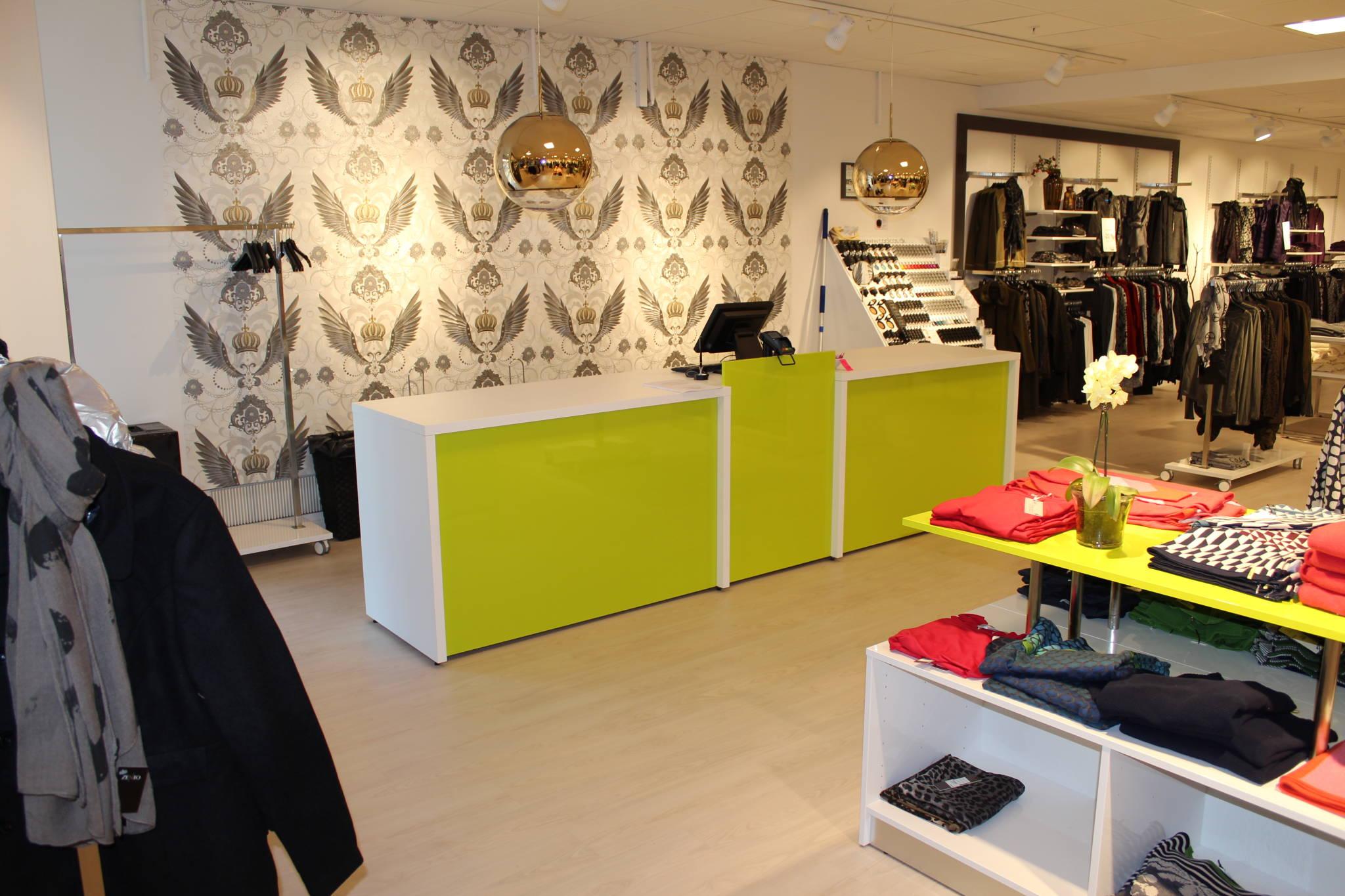 Butiksdesign og butiksinventar med en flot butiksdisk og mange lækre detaljer med tapeter, lamper, farver m.m. Butiksinventar i flotte farver