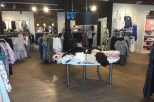 Butiksindretning med runde borde, butiksinventar og mannequiner