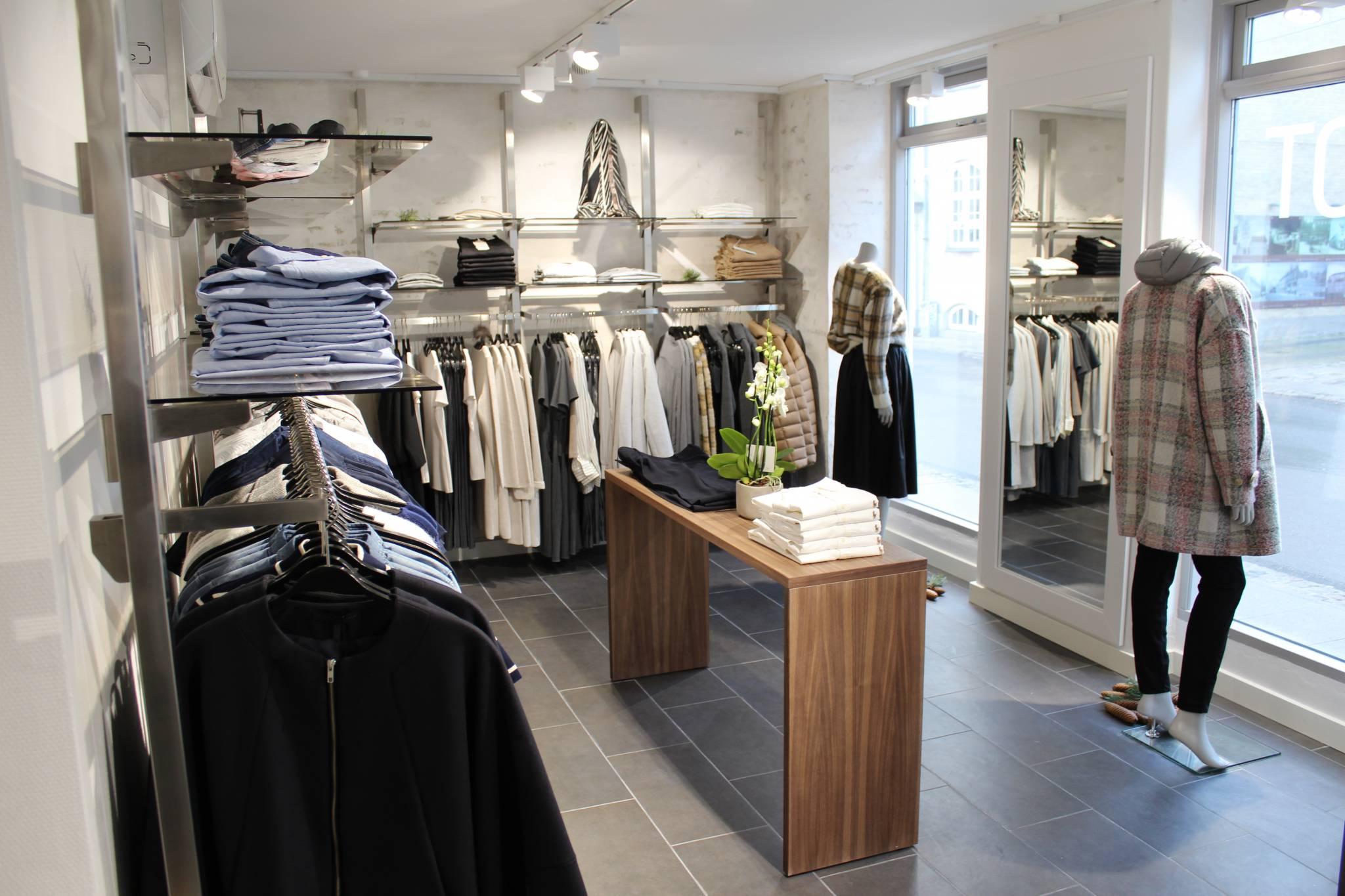 Butiksinventar med bl.a. flotte borde i Valnød og et flot og fleksibelt vægsystem. Væginventar og butiksindretning.
