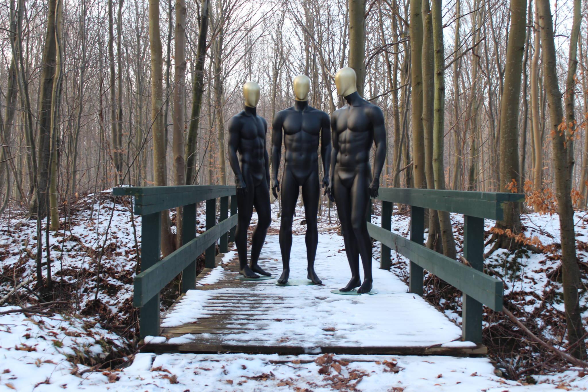 Flotte herre mannequiner i sort med guld malede hoveder.