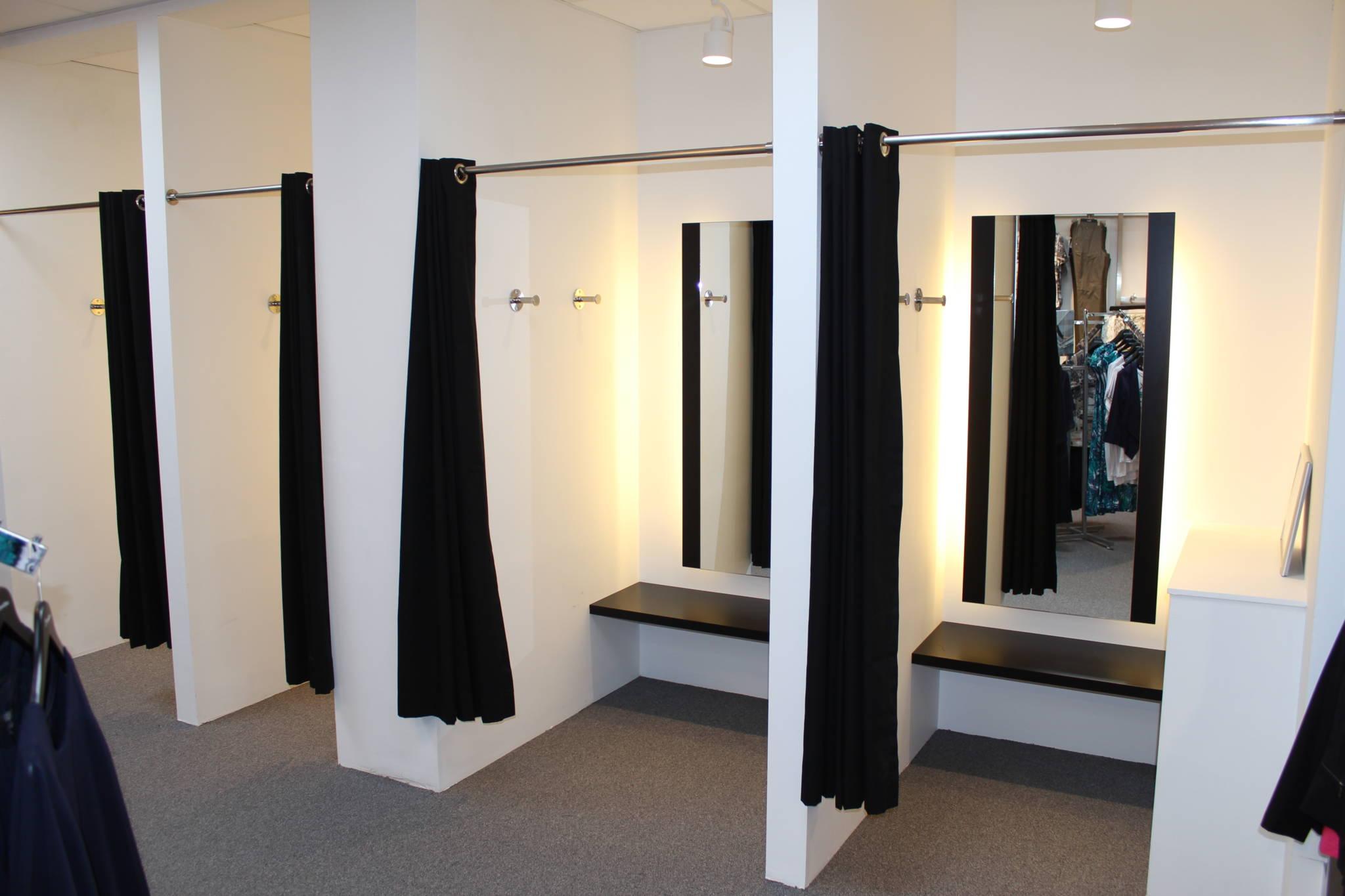 Store rummelige prøverum med fastmonterede bænke og lys bag spejlene.