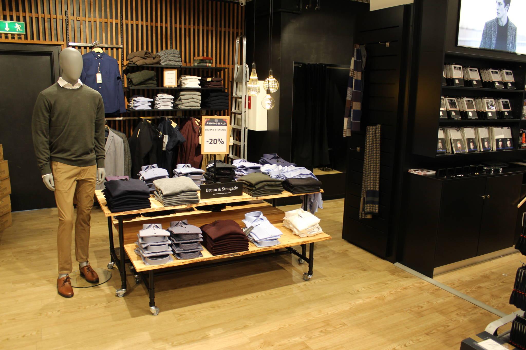 Trendy indrettet herrebutik med nøddefarvet lamelvæg. Butiksindretning og butiksinventar