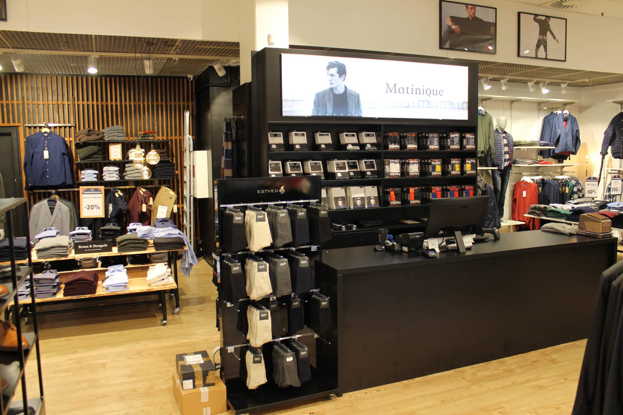 Trendy indrettet herrebutik med nøddefarvet lamel væg og sort diskområde. Butiksindretning og butiksinventar