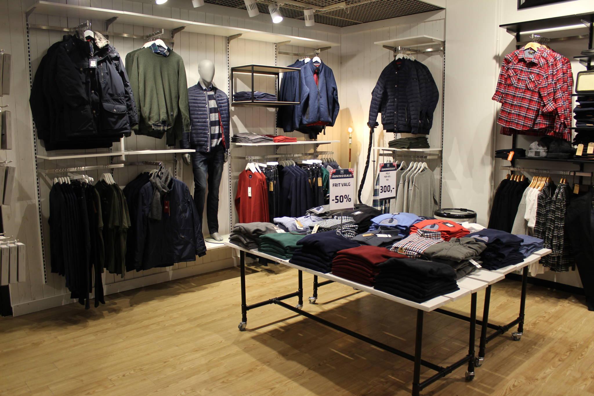 Trendy indrettet herrebutik med rustik bræddevæg. Butiksinventar og butiksindretning