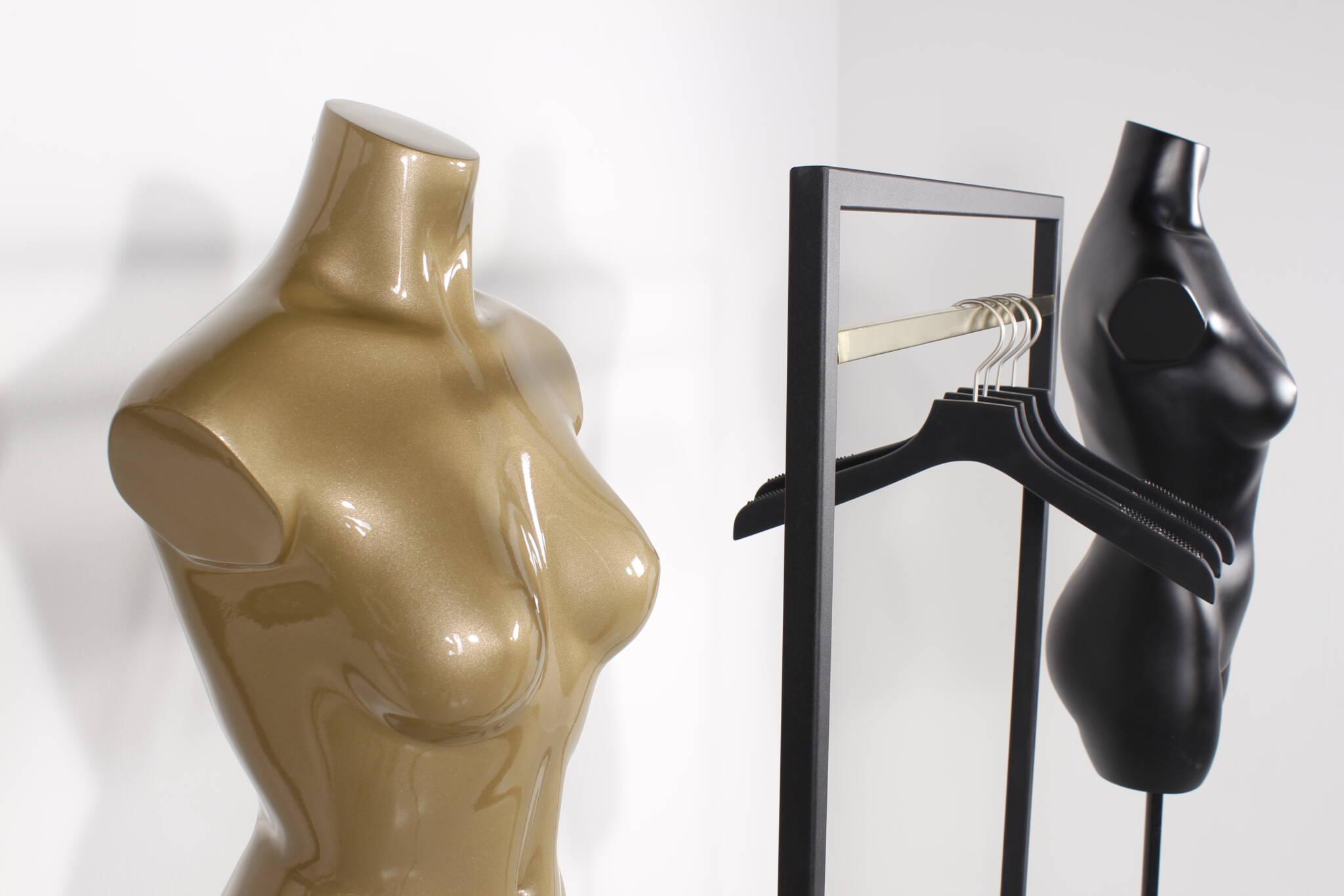 Designer stativ o sort med messing bøjlestang vist sammen med torsoer malet i guld farve